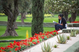 A delegate prays in the gardens