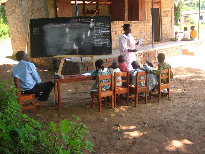 Mr. Clément Feizouré (left), Director of Ahdieh Foundation, visits a class at a community school in Bangui.
