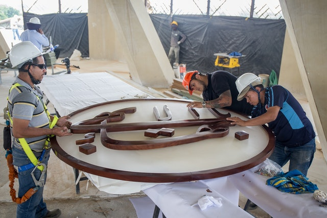 Carpenters from the firm that carved the Greatest Name symbol prepare it to be raised to the apex of the dome of the local House of Worship in Agua Azul, Colombia.