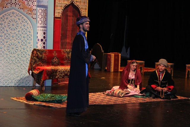 An actor playing Tahirih's cousin, who played an important role in connecting her to the intellectual and religious thought movements in society, speaks with two other relatives of Tahirih in a scene of the play.