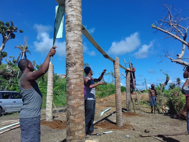 In the months following September 2017, when Hurricane Maria devastated the Caribbean island of Dominica, the community united in reconstruction efforts. Here, youth and adults work together to build a greenhouse in the island's Kalinago territory.