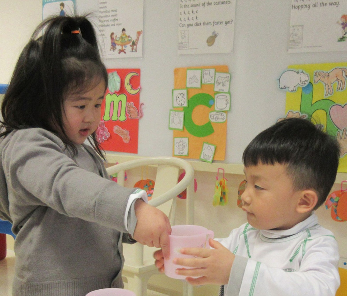 Service is integrated into the School of the Nations' curriculum. Here, a kindergarten student offers water to her classmate as part of a lesson.