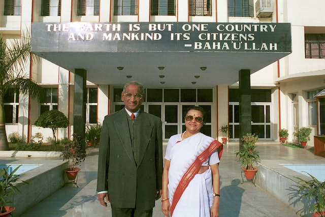 "Jagdish Gandhi and Bharti Gandhi, founders of the City Montessori School in Lucknow, India.| They are standing in front of the main building of Gomti Nagar branch of the School, one of 20 branches in Lucknow. A quote from Bahá'u'lláh, ""The earth is but one country and mankind its citizens"" is on the awning behind them."